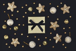 Christmas flat lay with golden gift box surrounded by shiny star, tree bauble and bell ornaments on black background