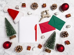 Christmas flatlay with blank notebook, fir trees, balls, conifer, presents, envelope, reindeer and Santa's hat in red, green, white on marble background. Copy space for wish list or new year 2021 plan