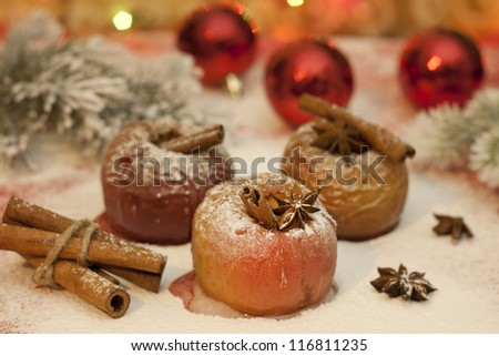 Christmas food baked apples and baubles on blurred background