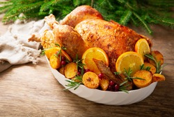 Christmas food. Baked turkey garnished with potato, oranges and  cranberries on a wooden table