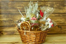 Christmas food gift baskets. Edible Christmas gift made of cookies, honey, homemade handmade sweets, dried oranges, lollipops on a wooden table.Concept handmade christmas gifts, Handmade food presents