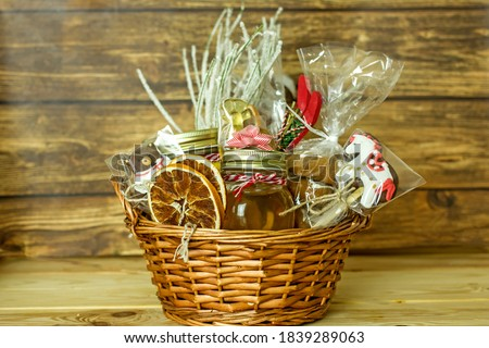 Christmas food gift baskets. Edible Christmas gift made of cookies, honey, homemade handmade sweets, dried oranges, lollipops on a wooden table.Concept handmade christmas gifts, Handmade food presents Stock photo ©