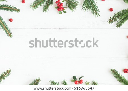 Christmas frame made of fir branches, red berries. Christmas wallpaper. Flat lay, top view