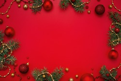 Christmas frame of fir tree and decorations on red background. Copy space, holiday flat lay.