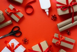 Christmas frame of gift boxes, wrapping craft paper, scissors, glue and decorations on red background, space for text