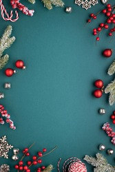 Christmas frame with classic decorations. Fir branches, red balls, jingle bells on turquoise background.