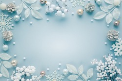 Christmas frame  with festive decorations, snowflakes, baubles on pastel background. Flat lay. Top view, copy space.