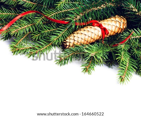 Christmas Frame with Fir Tree Branch and Christmas decoration isolated on white background. Evergreen Border with cone and red ribbon close up.