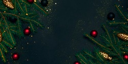 Christmas frame with fir tree branches, balls, glitter and confetti on black background. Holiday concept. Flat lay, top view with copy space