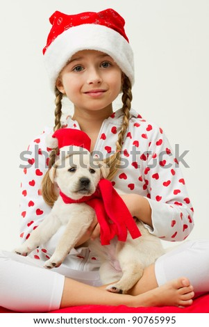 Christmas friends - little girl with cute puppy in a Santa hat