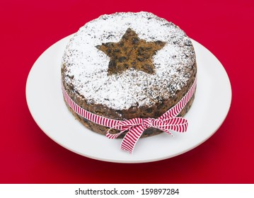 A stock photo of a Christmas Fruit cake on a red background