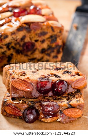 Christmas fruitcake slices garnished with cherries almonds and brazil nuts on chopping board.