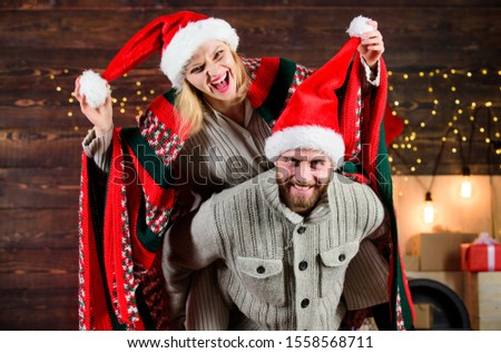 Christmas fun. Interesting ideas celebration. Man and woman santa claus hats cheerful celebrating new year. Merry christmas. Guy piggybacking girl. Celebrating together. Celebrating winter holiday.