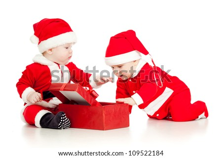 Christmas funny small kids in Santa Claus clothes with gift box