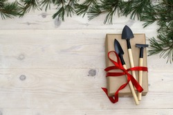 Christmas gardening tools on white wooden table. Top view, flat lay