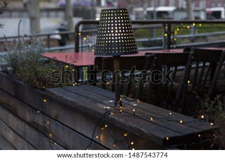 Christmas garland on the terrace. An evening lamp illuminates the wooden interior. #1487543774
