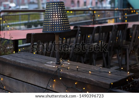 Christmas garland on the terrace. An evening lamp illuminates the wooden interior. #1490396723