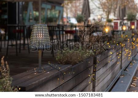 Christmas garland on the terrace. An evening lamp illuminates the wooden interior.