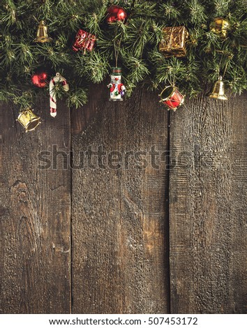 Christmas garland with toys and gifts on a dark wooden background. #507453172