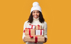 Christmas Gift. African American Woman Holding Many Present Boxes Posing On Orange Studio Background. Winter Holidays Celebration, New Year Offer Advertisement And Xmas Gifts Concept