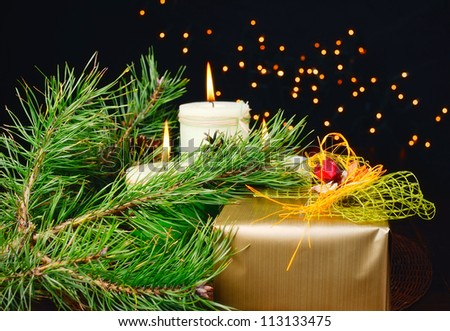 Christmas gift and candle on black background of defocused golden lights.