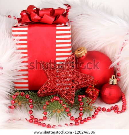 Christmas gift and red christmas balls in white fur