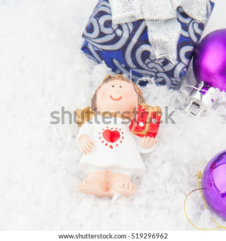 Christmas gift, angel toy and ball on snow #519296962