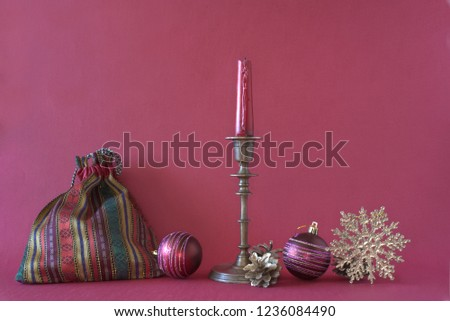 Christmas gift bag, candlestick with red candle, Christmas balls, golden snowflake and fir cones on a purple background #1236084490