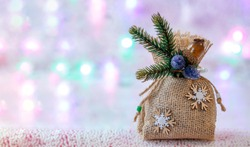 Christmas gift bag made of burlap, decorated with snowflakes and a fir branch on an unfocused background with garlands of lights. Festive, Christmas background. Free space for copying