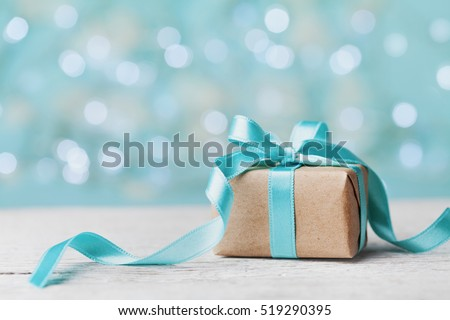 Christmas gift box against turquoise bokeh background. Holiday greeting card. #519290395