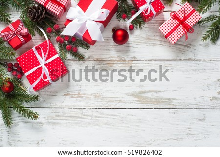 Christmas gift box.  Christmas presents in red boxes at white wooden table. Flat lay with copy space.