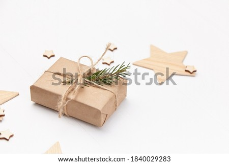 Christmas gift box decorated with green fir tree branch on white background, winter holidays concept