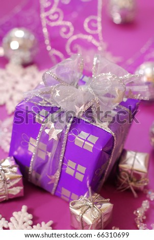 christmas gift box in purple color with silver ribbon on pink background