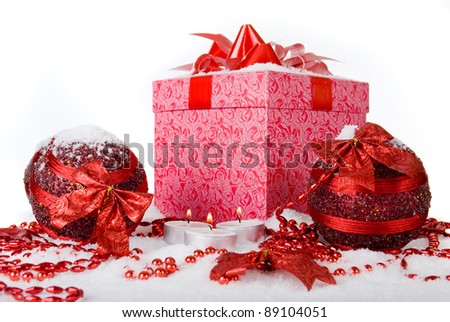 Christmas gift box in the snow with red balls and candles - stock photo