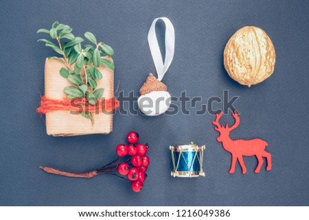 Christmas gift-box, nut, berry, a stencil of deer, decorative acorn and drum on the dark blue background.
