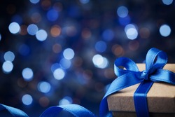 Christmas gift box or present with bow ribbon on magic blue bokeh background. Copy space for greeting text.