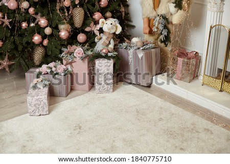 Christmas gift box under Chrismas tree lies on white carpet near fireplace Holiday morning. New year present paper package. Festive mood