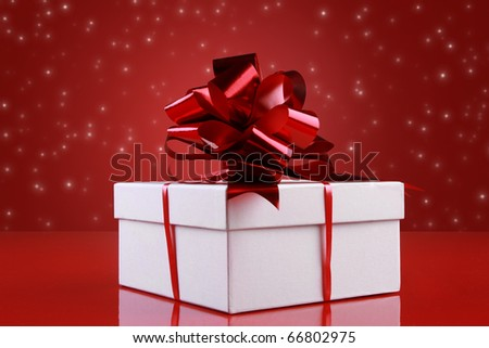 Christmas gift box with a dark-red satin ribbon bow on red background with snowflakes