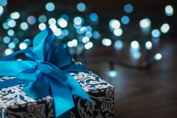 Christmas gift box with blue bow and bokeh lights on wooden surface