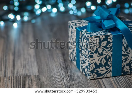 Christmas gift box with blue bow and bokeh lights on wooden surface #329903453