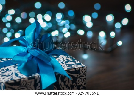 Christmas gift box with blue bow and bokeh lights on wooden surface #329903591