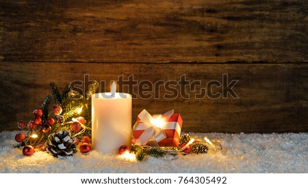 Christmas gift box with burning candle, lights and decorations at snow with wooden background