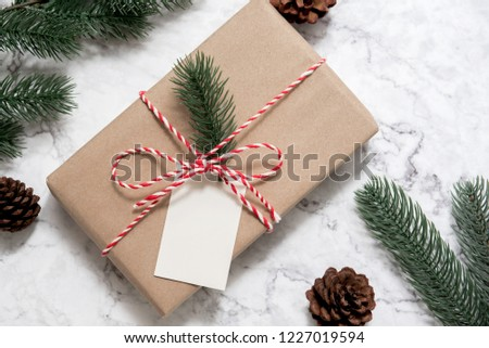 Christmas gift box with note card and tree branch decor on marble background. Flat lay, Top view with copy space Stockfoto ©