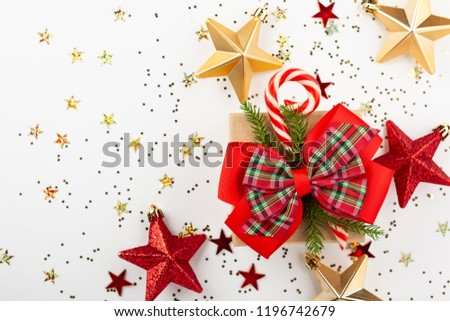 Christmas gift box with red ribbon and candy cone on white background. Top view. #1196742679