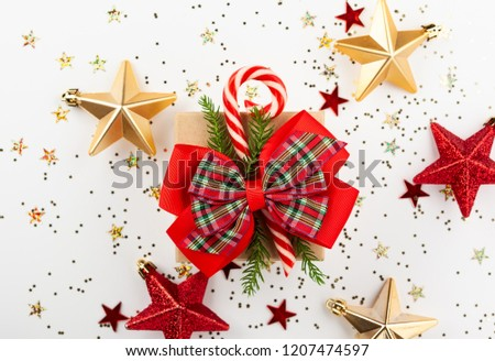 Christmas gift box with red ribbon and candy cone on white background. Top view. #1207474597