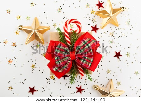 Christmas gift box with red ribbon and candy cone on white background. Top view. #1221444100