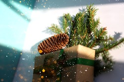 Christmas gift box wrapped in brown kraft paper and green ribbon with pine cone and tiny fir branches on the white background with flickring lights. Sustainable living concept. Minimalism decoration