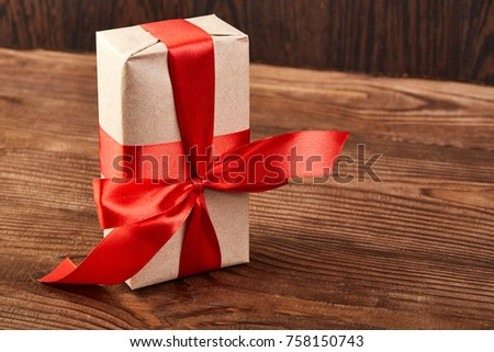 Christmas Gift boxes and decorations. Gift box in kraft paper with a red ribbon on a wooden background. Christmas background. #758150743