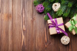 Christmas gift boxes and fir tree on wooden table. Top view with copy space