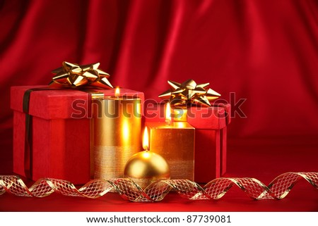 Christmas gift boxes decorated with candles and ribbon